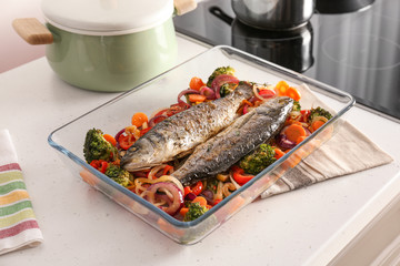 Baking tray with tasty fish and vegetables on kitchen table