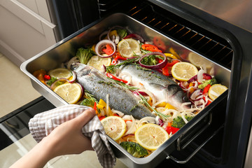 Papiers peints Poisson Woman putting baking tray with fish and vegetables into oven