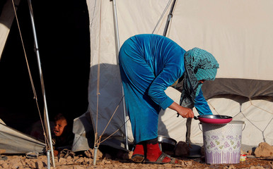 A woman prepares to cook a meal outside her family's tent at a refugee camp for people displaced by fightings between the Syrian Democratic Forces and Islamic State militants in Ain Issa