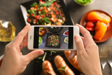Female blogger taking photo of food with smartphone indoors