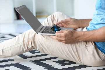 Man holding credit card while using laptop at home
