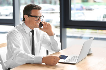 Young businessman holding credit card while making call at workplace