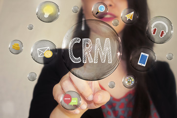 Portrait of a beautiful young woman pointing her finger to CRM in transparent bubble