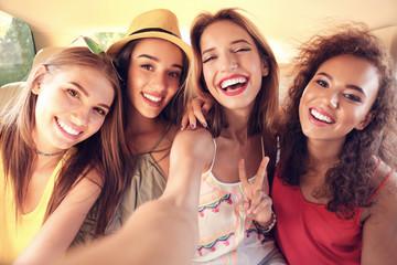 Beautiful young women taking selfie in car