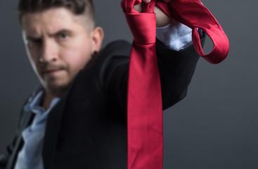 Genervter Businessmann zieht seine Krawatte aus und kündigt seinen Job