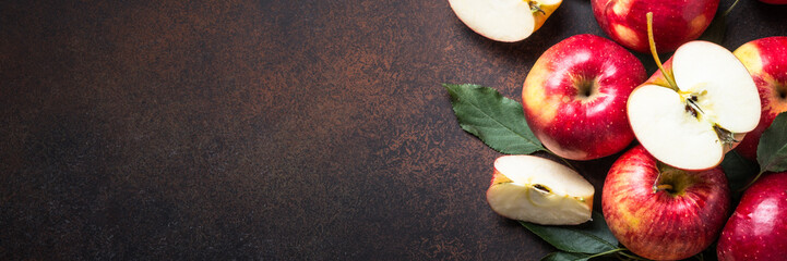 Red apples with leaves on the table. Long banner format.