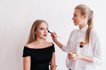 Professional makeup artist working with beautiful young woman in black dress on white background