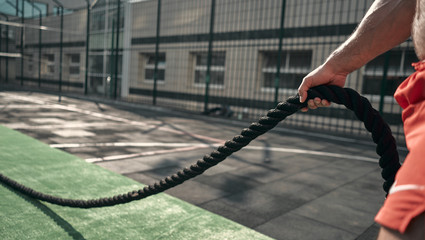 Close-up. Athletic man pulling the rope. Sport equipment. Outdoors. Green colors. Sports ground.