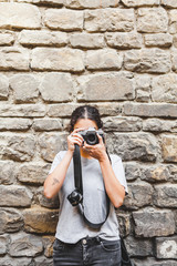 Young Photographer with Analog Camera in front of an Old Stone Wall
