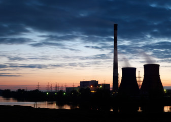 Silhouette of gas turbine electrical power plant against sunset sky