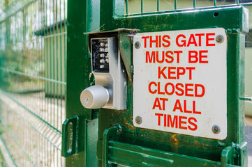 Sign on a security gate advising that it must be kept closed.