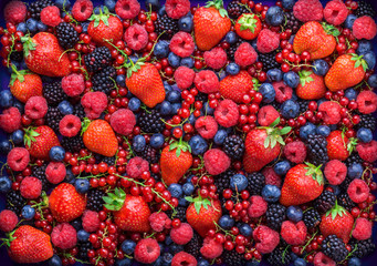Photo sur Plexiglas Fruit Berries overhead closeup colorful large assorted mix of strawbwerry, blueberry, raspberry, blackberry, red curant in studio on dark background