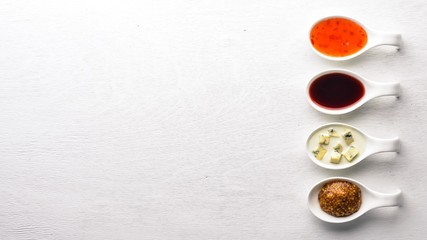 A set of sauces and spices. On a wooden background. Top view. Free space for text.
