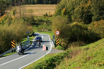 Motocykliści na zakręcie drogi w Ojcowskim Parku Krajobrazowym.