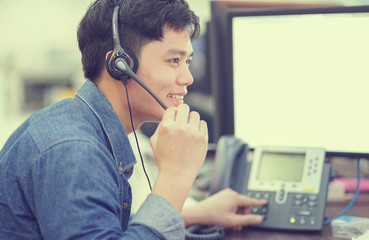 close up asian call center employee man working smiling with service-mind