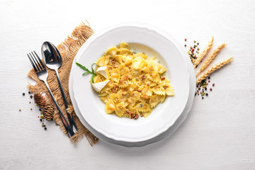 Pasta four cheeses. Italian food. On a wooden background. Top view. Free space for text.