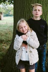 Siblings standing under a tree.