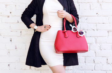 Woman in black coat hold red handbag in hand. Stylish accessory