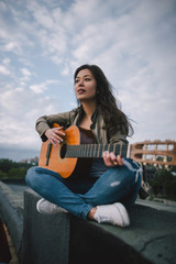 Free music. Female guitarist plays guitar on the street. Freedom, leisure, live concert, young bard and composer concept