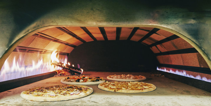 Pizza into the wood oven