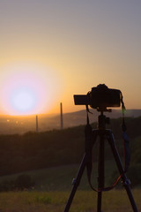 camera on tripod taking picture of  landscape during the sunrise