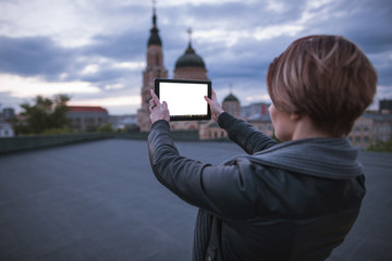 Girl takes pictures of the city on a tablet. Girl takes pictures of the city on a tablet. Tourist near attractions. A traveler uses a digital gadget for photos