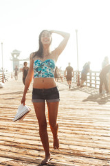 Smiling skinny young woman walking on a pier barefoot