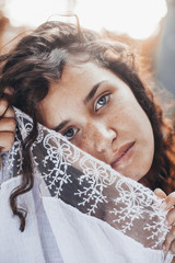 Beautiful young woman with curly hair, blue eyes and freckles
