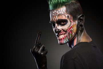 Side view if a man with colored skull makeup showing long finger. Face art, man with zombie face.