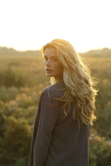 young woman with blonde hair, in nature, at sunset