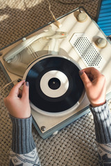 Young woman placing vinyl on 60s record player