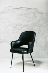 Black armchair on white wall.