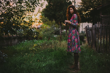 Beautiful young woman in floral dress with camera in the garden