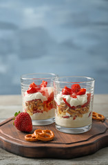 Glasses with strawberry pretzel salad on wooden board