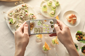 Blogger making photo of food with cell phone