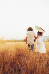 Romance - Good-Looking Young Couple Walking Together in Dry Grassland