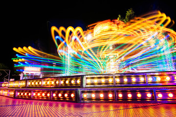 Long exposure shot of carousel attraction in a fair at night with colorful lights