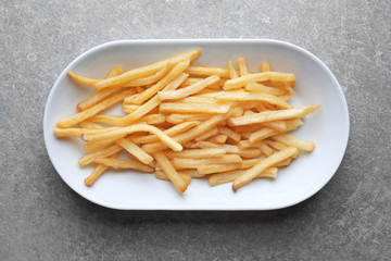 Plate with yummy french fries on kitchen table