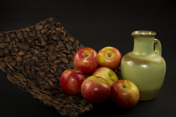 Apples and a Green Vase in a Basket and Black Background
