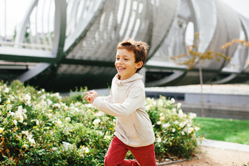 Smiling little boy running in the park.