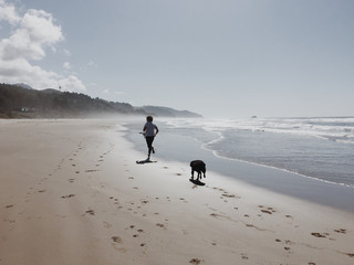 Man running on the beach with his dog