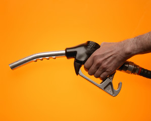 Hand holding petrol pump on yellow background