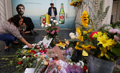 A woman places a flower on the star of Tom Petty and the Heartbreakers on the Hollywood Walk of Fame in Los Angeles