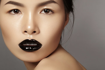 Close-up portrait asian model with fashion lips make-up, clean skin. Beauty halloween style with black lipstick makeup