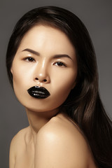 High Fashion Beauty Asian Model with bright Lip Gloss Make-up. Black Lips with gloss lipstick makeup. Long dark hair