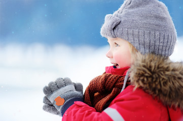 Portrait of little boy in red winter clothes having fun with snow