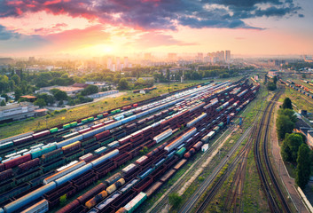 Cargo trains. Aerial view of colorful freight trains. Railway station. Wagons with goods on railroad. Heavy industry. Industrial scene with trains, city buildings and cloudy sky at sunset. Top view
