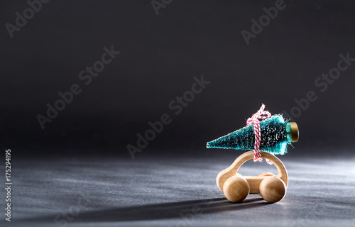Miniature wooden car carrying a Christmas tree on a black backdrop