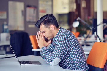 Businessman feeling headache while doing distance work in coffee shop tired with failure of plans