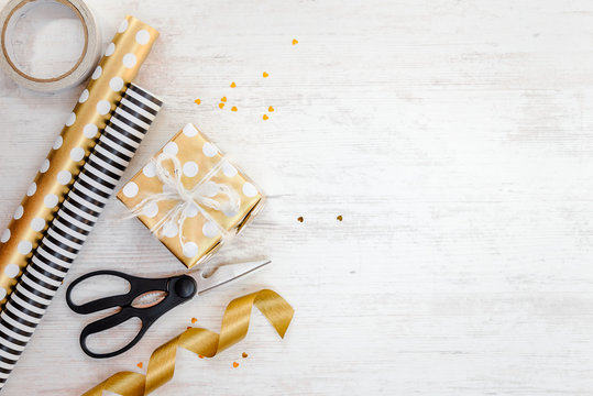 Gift box wrapped in golden dotted paper and wrapping materials on a white wood old background. Empty space.